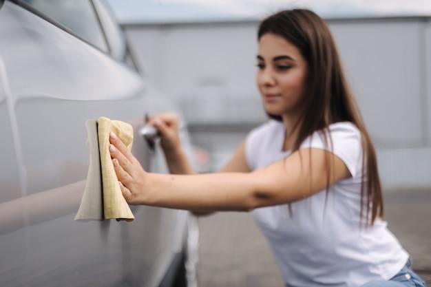 Une conductrice séduisante et joyeuse essuie sa voiture à l'aide d'un chiffon dans un lave-auto en libre-service