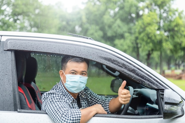 Conduire en toute sécurité par jour de pluie. les asiatiques portant un masque sont assis dans la voiture et les pouces vers le haut. effet de lumière parasite