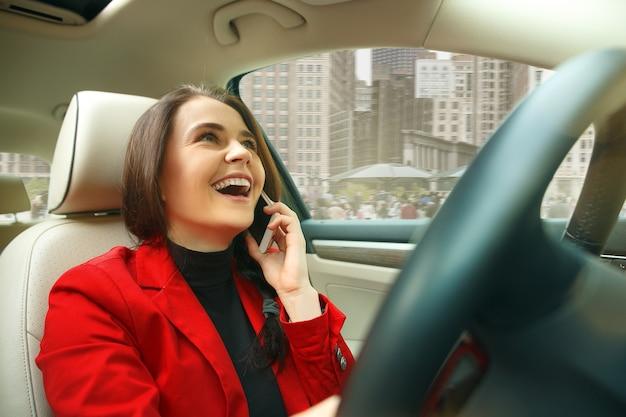 Conduire en ville. jeune femme séduisante au volant d'une voiture. jeune modèle assez caucasien en veste rouge élégante et élégante assis à l'intérieur du véhicule moderne