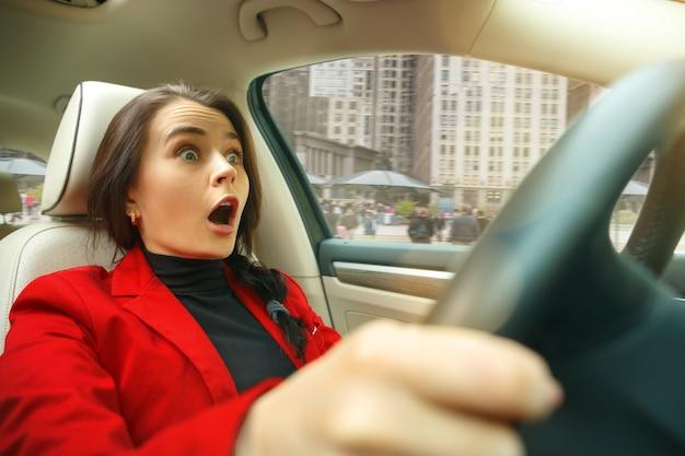 Conduire en ville. jeune femme séduisante au volant d'une voiture