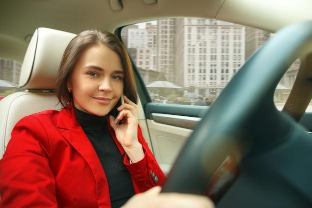 Conduire en ville. jeune femme séduisante au volant d'une voiture.