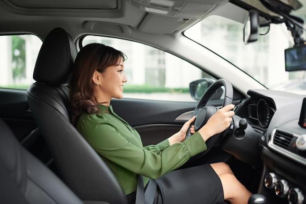 Conduire en ville. jeune femme séduisante souriante et regardant droit en conduisant une voiture