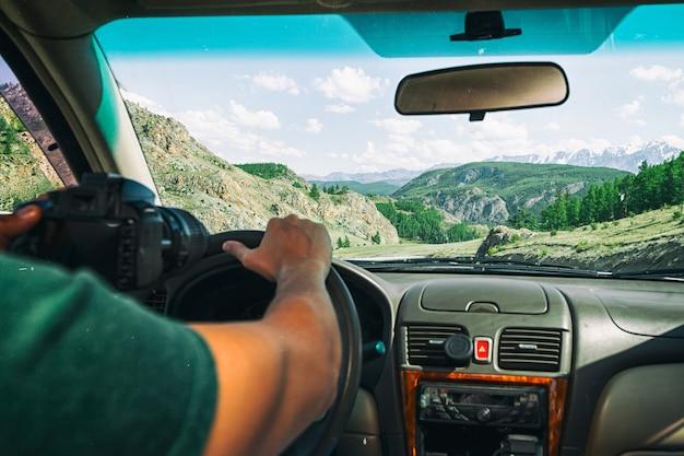Conduire une voiture sur la route de montagne. guy à l'intérieur de la voiture roulant sur la route de campagne entre les champs avec de l'herbe brune et des montagnes enneigées. le soleil brille. tirez par l'arrière.