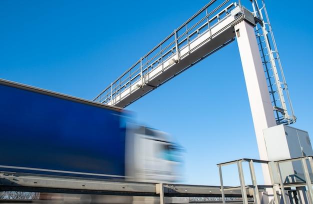 Conduite de camion sur l'autoroute par la barrière de péage, frais de péage, mouvement flou dans l'image