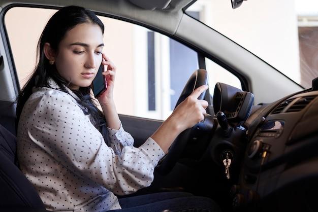 Conduite dangereuse jeune femme multiraciale parlant au téléphone tout en conduisant une femme distraite au volant
