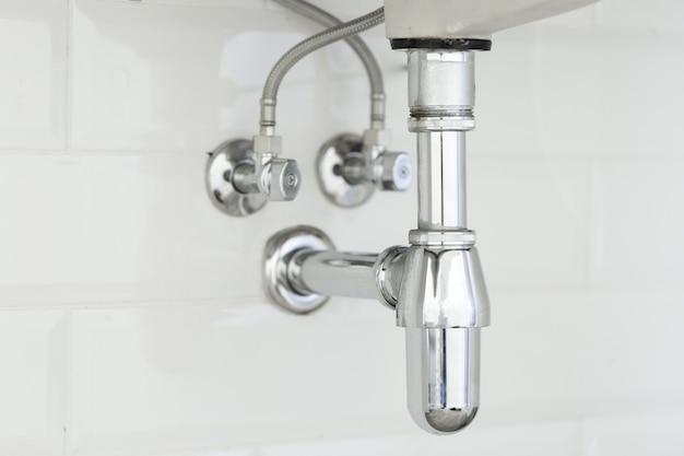 Conduite d'eau sous l'évier sur blanc