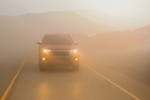 Conduite de voitures dans la montagne de brouillard avec des faisceaux de phares dans une brume dense.
