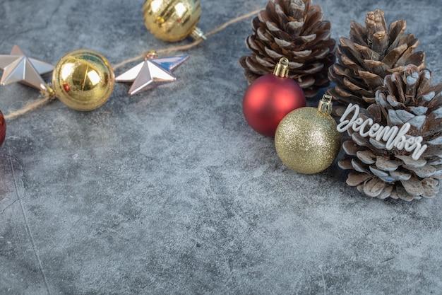 Cône d'arbre de noël avec l'écriture de décembre dessus et des chiffres scintillants autour