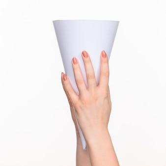 Le cône blanc des accessoires dans les mains féminines sur blanc avec ombre droite