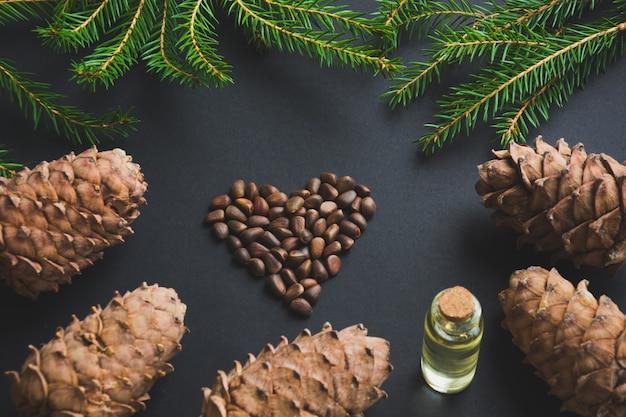 Cône de cèdre, branches, huile de cèdre et noix en forme de cœur sur fond noir.