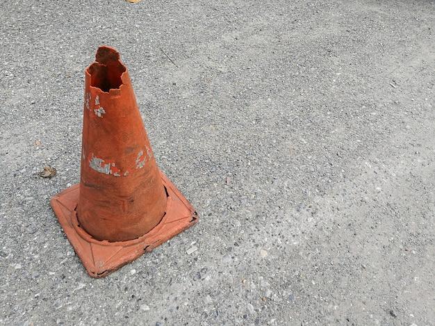 Cône de circulation orange sur route asphaltée avec une flèche blanche pour tourner à gauche devant.