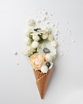 Cône de gaufre avec bouquet de fleurs et meringues sur fond blanc, mise à plat, vue de dessus