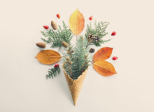 Cône de gaufre avec composition de branches, de feuilles et de strobiles de conifères