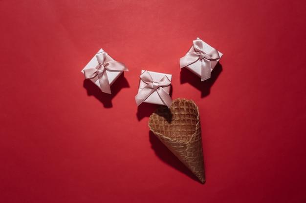 Cône de gaufre de crème glacée avec des coffrets cadeaux sur fond rouge clair. vue de dessus