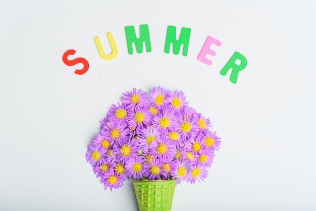 Cône de gaufre avec des fleurs d'aster alpin sur un concept de fond blanc, texte d'été. mise à plat, vue de dessus