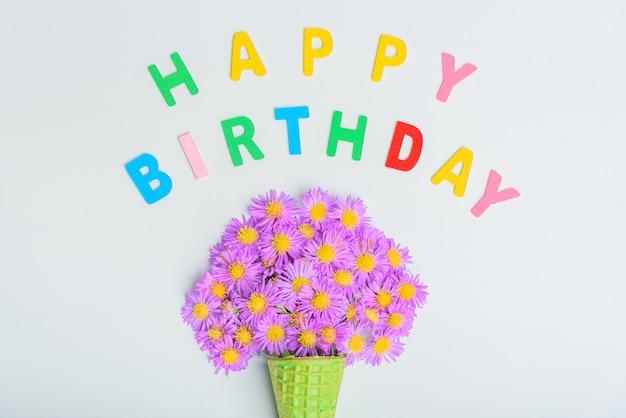Cône de gaufre avec fleurs aster alpin sur fond blanc, texte de joyeux anniversaire. mise à plat, vue de dessus