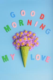 Cône de gaufre avec des fleurs d'aster alpin sur fond bleu le concept du 8 mars, texte bonjour