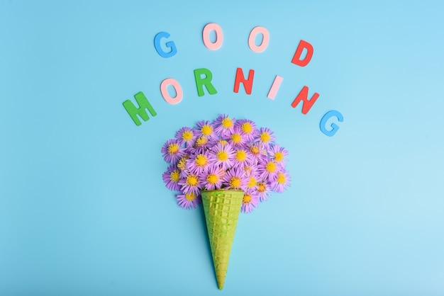 Cône de gaufre avec des fleurs d'aster alpin sur fond bleu. . texte bonjour. mise à plat, vue de dessus