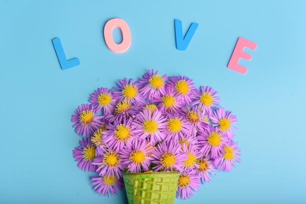 Cône de gaufre avec des fleurs d'aster alpin sur fond bleu. le texte est amour. mise à plat, vue de dessus.