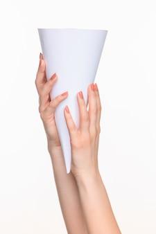Le cône en mains féminines sur un espace blanc