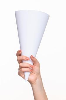 Le cône en mains féminines sur mur blanc