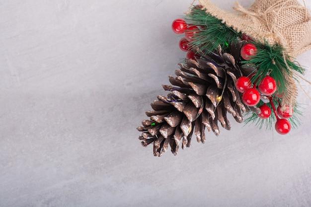Cône de pin décoré de baies de houx et flocon de neige sur une surface blanche