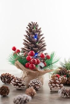 Cône de pin décoré de baies de houx et de lumières sur table en bois.
