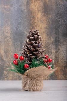 Cône de pin décoré de baies de houx sur tableau blanc.