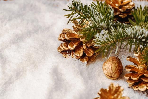 Cône de pin peint en or sur table enneigée, décor de noël
