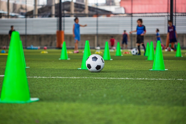 Cône de tactique de ballon de football sur le terrain d'herbe avec pour le fond de formation formation des enfants au football