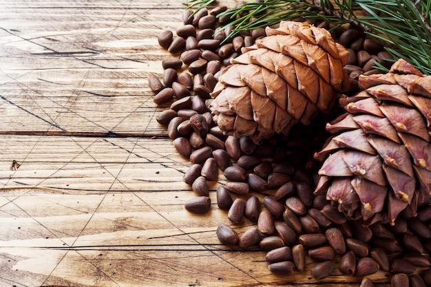 Cônes de cèdre et noix sur une table en bois.