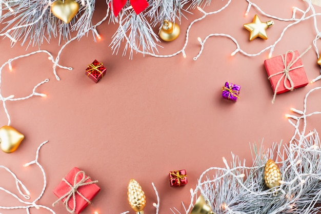 Cônes de conifères, flocons de neige, cadeaux et lumières de noël sur un fond chaud
