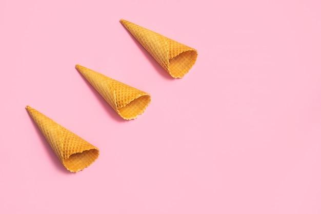 Cônes de crème glacée vides sur une table rose tendre