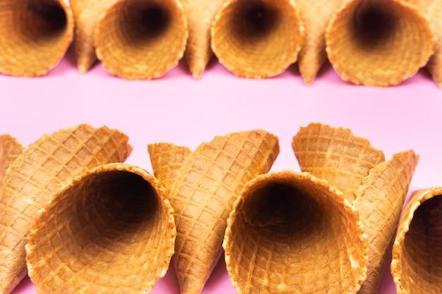Cônes de gaufres vides pour la crème glacée sur fond rose.
