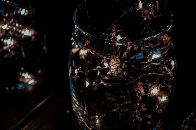 Cônes avec guirlande dans un vase en verre noël noël vacances nouvel an hiver lumière décorations festives