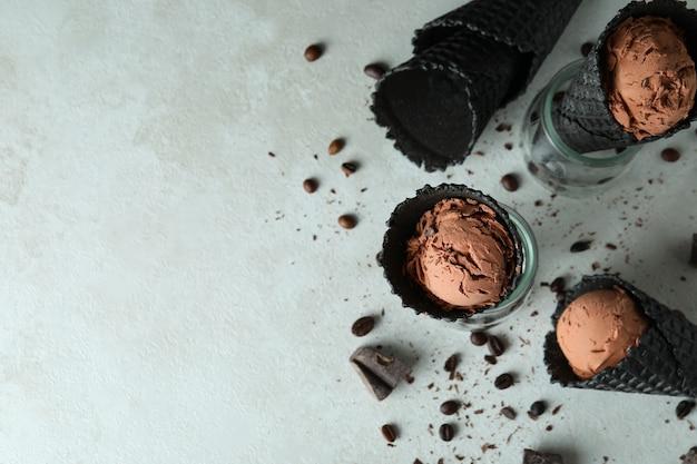 Cônes noirs avec de la crème glacée sur blanc texturé