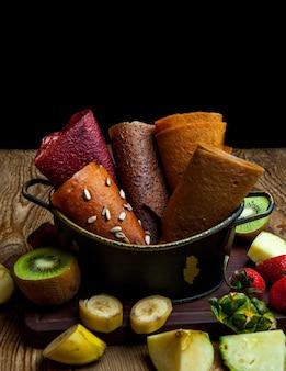 Cônes de pastila aux fruits dans le panier avec des fruits frais