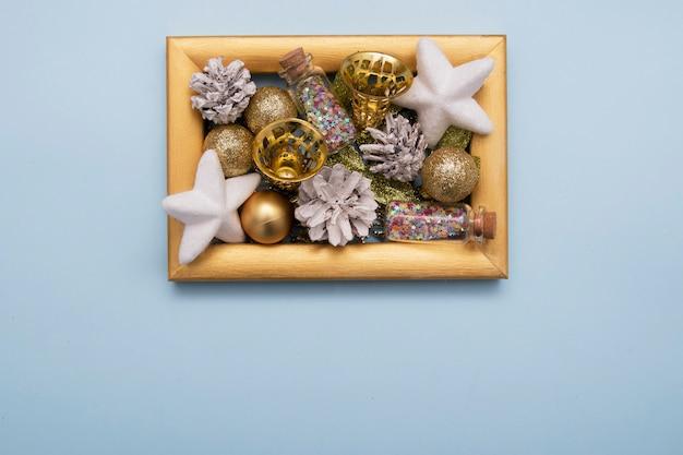 Cônes de pin blanchis à la chaux, cloches et autres décorations de noël nouvel an dans un cadre photo doré sur fond bleu télévision lay