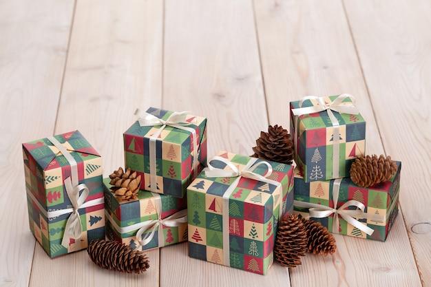 Cônes de pin de noël et boîtes de fête avec des cadeaux sur un fond en bois clair.