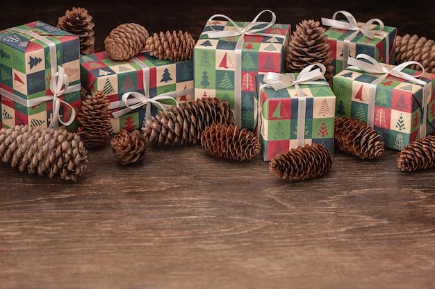 Cônes de pin de noël et boîtes de vacances avec des cadeaux sur un fond en bois foncé.