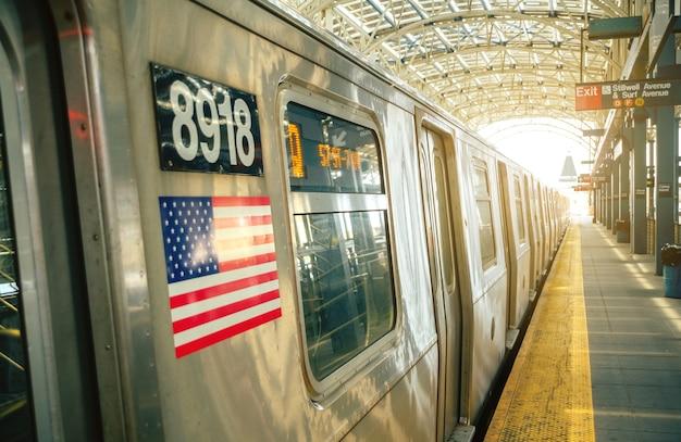 Coney island, new york - 26 juin 2016 : plate-forme vide avec train arrêté dans la station de métro