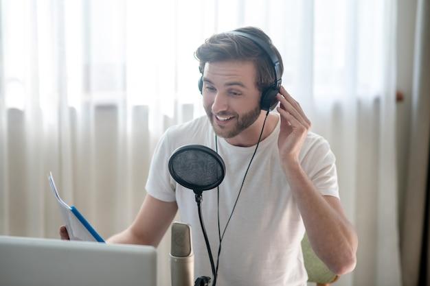 Conférence. jeune homme barbu assis dans un casque et parlant au microphone