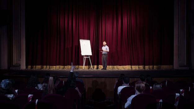 Conférence. orateur masculin faisant une présentation dans le hall de l'atelier. centre d'affaires. vue arrière des participants en public. conférence événement, formation. éducation, réunion, concept d'entreprise.