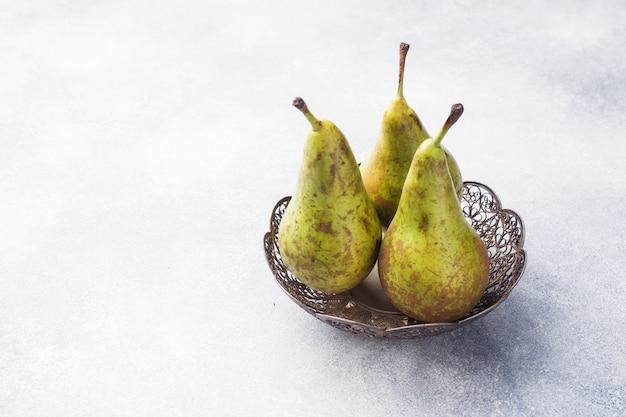 Conférence de poires juteuses fraîches dans un panier sur un fond gris.