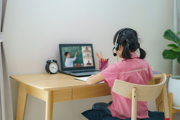 Conférence vidéo étudiante asiatique fille e-learning avec enseignant et camarades de classe sur ordinateur dans le salon à la maison.