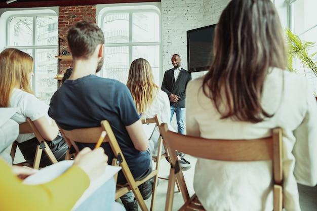 Conférencier afro-américain masculin faisant une présentation dans le hall de l'atelier. public ou salle. vue arrière des participants en public. conférence événement, formation. éducation, diversité, concept inclusif.