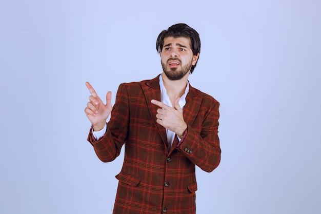 Un conférencier en blazer marron pointant vers la gauche et en parlant avec des émotions.