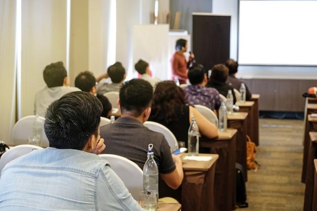 Conférencier à l'écoute du public qui se tient devant la salle dans la salle de conférence