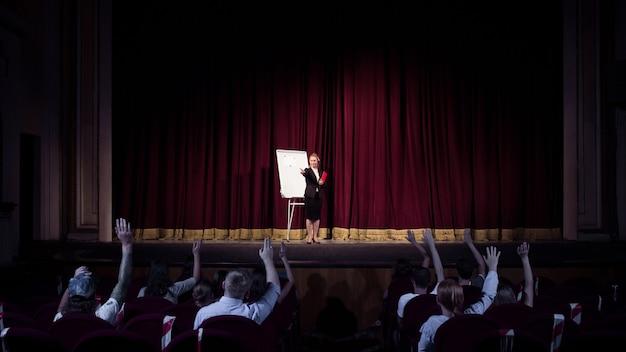 Conférencière caucasienne faisant une présentation dans le hall de l'atelier de l'université ou du centre d'affaires