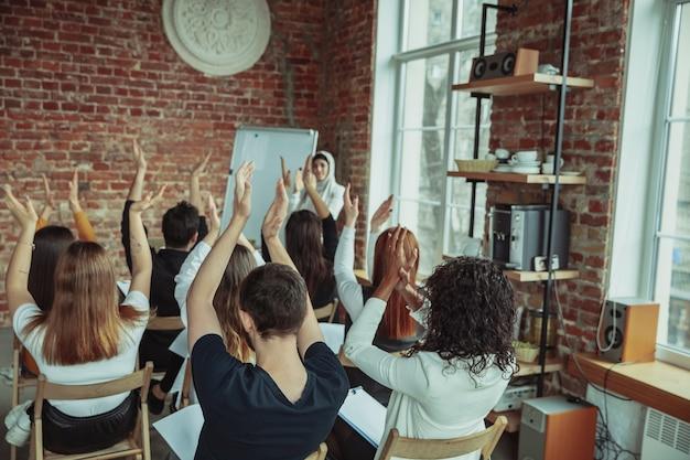 Conférencière musulmane faisant une présentation dans le hall de l'atelier. salle d'audience ou de conférence.